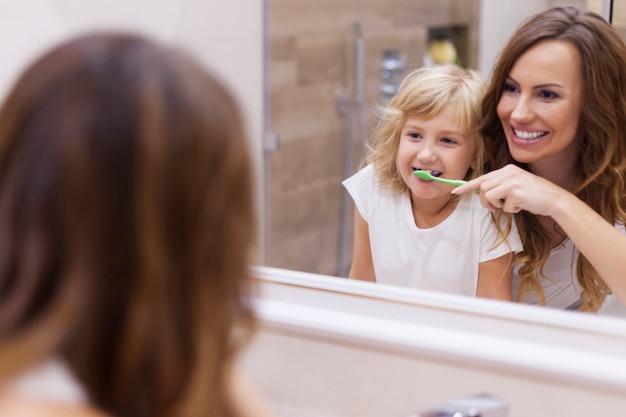 Lezione mattutina di lavarsi i denti con la mamma Foto Gratuite