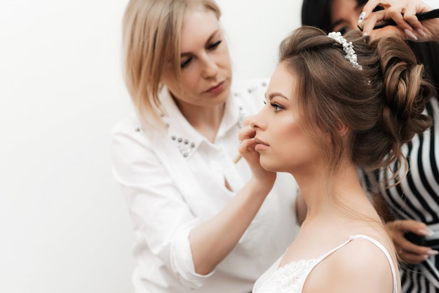 Morning Preparations For The Bride S Wedding In A Beauty Salon A Makeup Artist Does Make Up And A Hairdresser Does Her Hair Premium Photo