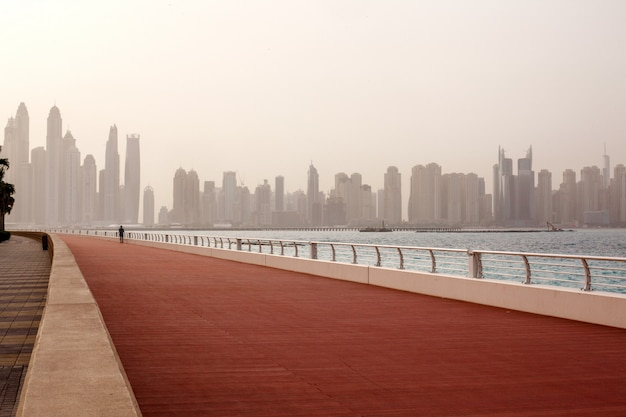 Morning run, a man runs along the road with a beautiful view of dubai. uae Premium Photo
