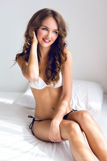 Mattina sensuale ritratto sexy di splendida giovane donna appena svegliata in camera da letto bianca, godersi il suo tempo mattutino, indossando lingerie casual carina, un trucco elegante e tenui colori pastello. Foto Gratuite