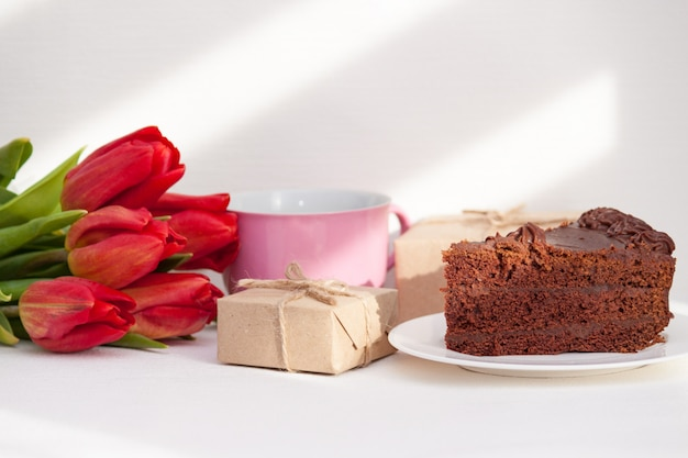 Morning. tulips, presents, cake, cup for mother, wife, daughter, girl with love. happy birthday, Premium Photo