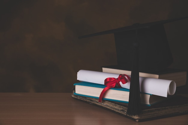 A mortarboard and graduation scroll, tied with red ribbon Premium Photo