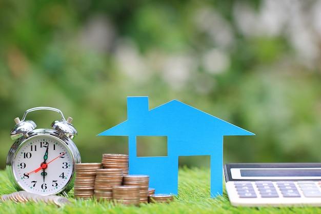 Ипотечный калькулятор, модель голубого дома и стопка монет с будильником, процентными ставками и банковской концепцией Premium Фотографии