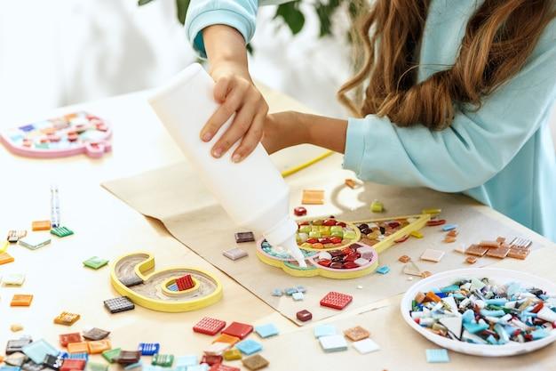子供のためのモザイクパズルアート、子供たちの創造的なゲーム。手はテーブルでモザイクを再生しています。カラフルなマルチカラーのディテールがクローズアップ。 無料写真