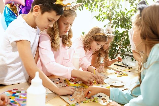 L'arte puzzle mosaico per bambini, gioco creativo per bambini. le mani giocano a mosaico al tavolo. i dettagli multicolori variopinti si chiudono su. creatività, sviluppo dei bambini e concetto di apprendimento Foto Gratuite