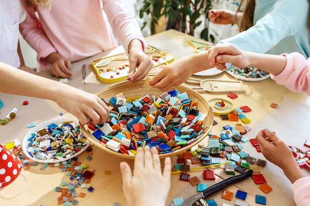 Mosaic puzzle art for kids, children's creative game. hands are playing mosaic at table. colorful multi-colored details close up. Free Photo