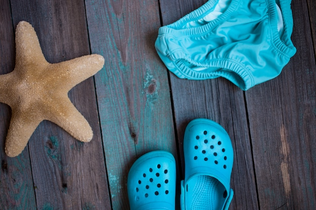 Moscow, russia - 05.28.2018: baby beach slippers, starfish, baby swimming trunks on wooden background Premium Photo