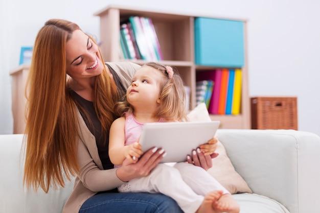 自宅でタブレットでゲームをしている母と赤ちゃん 無料写真