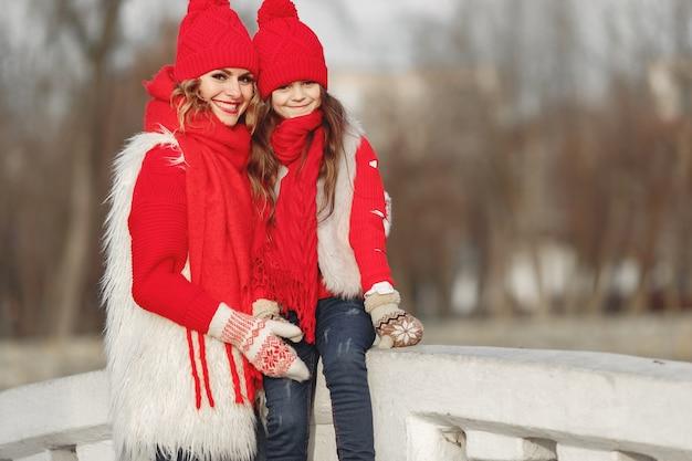 家族のクリスマス休暇にニットの冬の帽子をかぶった母と子。ママと子供のための手作りのウールの帽子とスカーフ。子供のための編み物。ニットアウター。公園の女性と少女。 無料写真