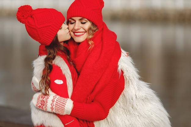 엄마와 가족 크리스마스 휴가에 니트 겨울 모자에 아이. 엄마와 아이를위한 수제 양모 모자와 스카프. 아이들을위한 뜨개질. 니트 겉옷. 여자와 공원에서 어린 소녀입니다. 무료 사진