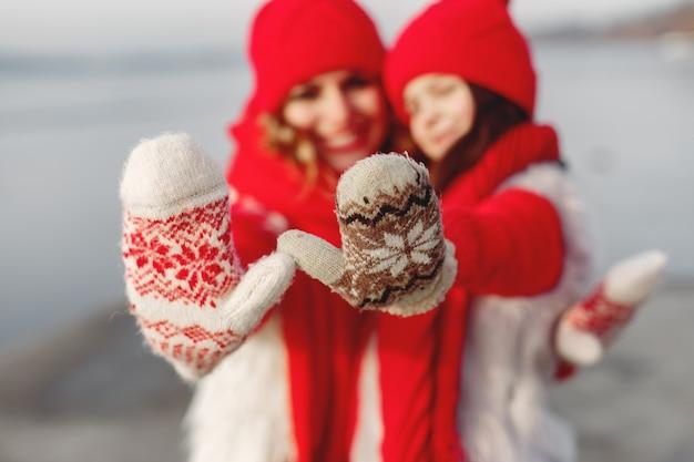 Мать и ребенок в вязаных зимних шапках на семейных рождественских каникулах. шерстяная шапка и шарф ручной работы для мамы и малыша. вязание для малышей. вяжем верхнюю одежду. женщина и маленькая девочка в парке. Бесплатные Фотографии