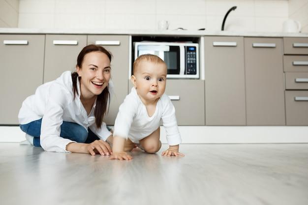 Мать и дитя, играя на кухонном полу, весело Бесплатные Фотографии