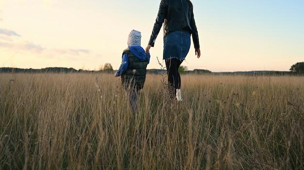母と子は日没時にフィールドを横切って歩きます。 Premium写真