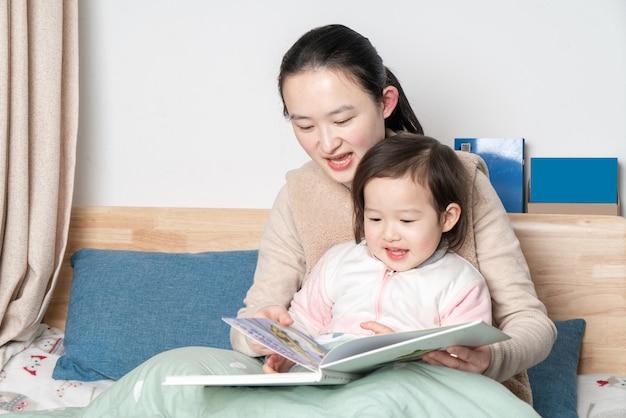 어머니와 딸이 침대에서 읽으십시오 프리미엄 사진