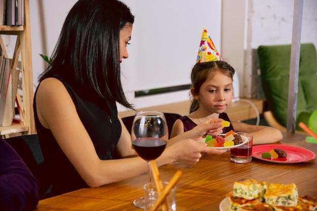 엄마와 딸 집에서 생일을 축하합니다. 큰 가족이 케이크를 먹고 와인을 마시면서 인사하고 아이들을 즐겁게합니다. 축하, 가족, 파티, 가정, 어린 시절, 부모 개념. 무료 사진