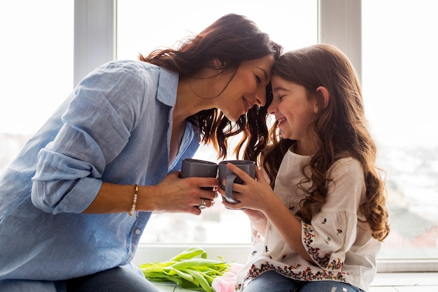 母と娘の窓枠にお茶を飲む Premium写真