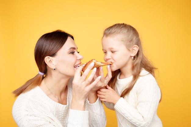 母と娘が一緒にピザを食べて、黄色いスタジオで孤立して楽しんでいます。 Premium写真