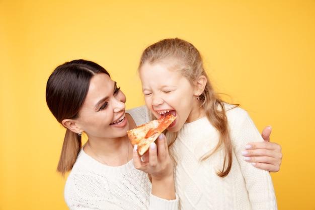 一緒にピザを食べる母と娘 Premium写真