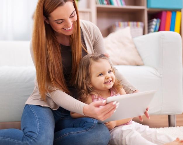Мать и дочь веселятся во время использования цифрового планшета Бесплатные Фотографии