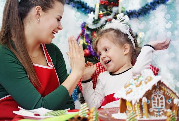 Мать и дочь весело украшают пряничный домик Premium Фотографии