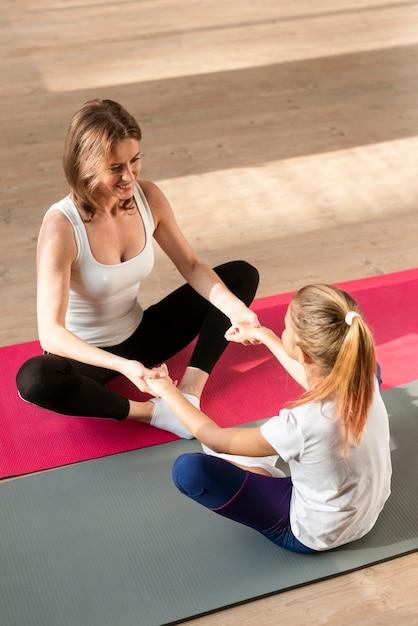 Мать и дочь, держась за руки на коврики для йоги Бесплатные Фотографии
