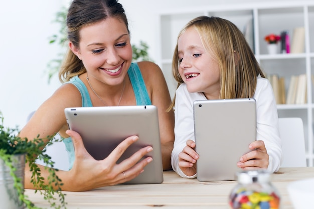 mother and daughter looking at tablets photo premium download