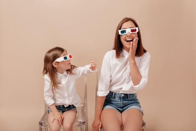 Мать и дочь, глядя друг на друга и улыбаясь в 3d-очках на камеру на диване, изолированном на бежевом фоне. Бесплатные Фотографии
