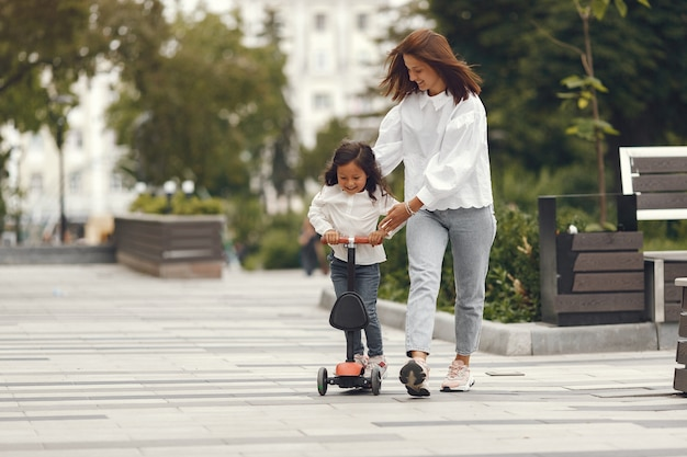 Мать и дочь на самокате в парке. дети учатся кататься на роликах. маленькая девочка на коньках в солнечный летний день. Бесплатные Фотографии