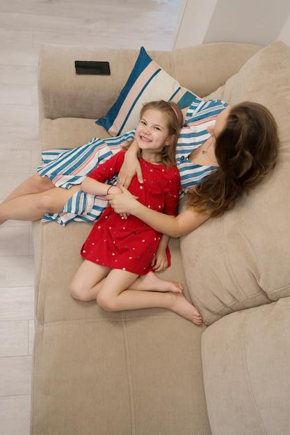 ソファーで横になっている母と娘の肖像画 無料写真