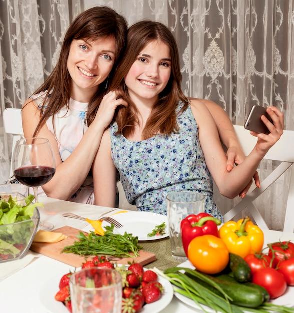 母と娘の夕食のテーブルでポーズ 無料写真