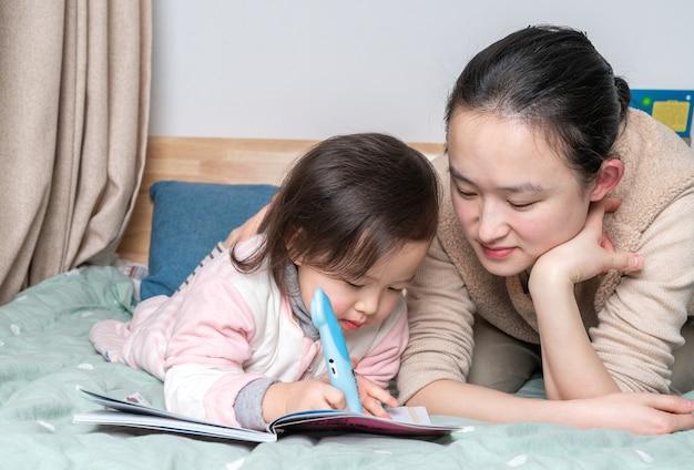 엄마와 딸이 함께 읽고 침대에 앉아 프리미엄 사진