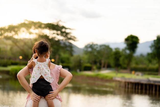 Мать и дочь сидят у пруда Premium Фотографии