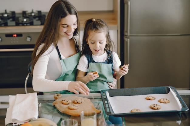 母と娘のクッキーが付いている台所に座っています。 無料写真