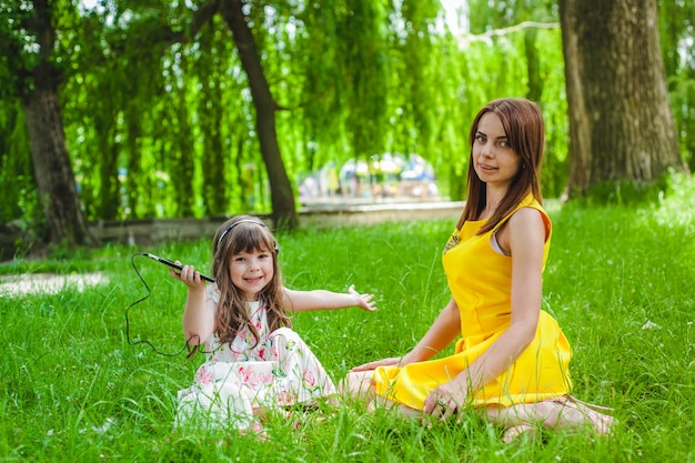Mother and daughter sitting on the lawn Photo