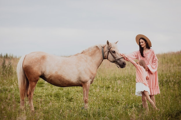 Mother and daughter stand on the field before a horse  Free Photo