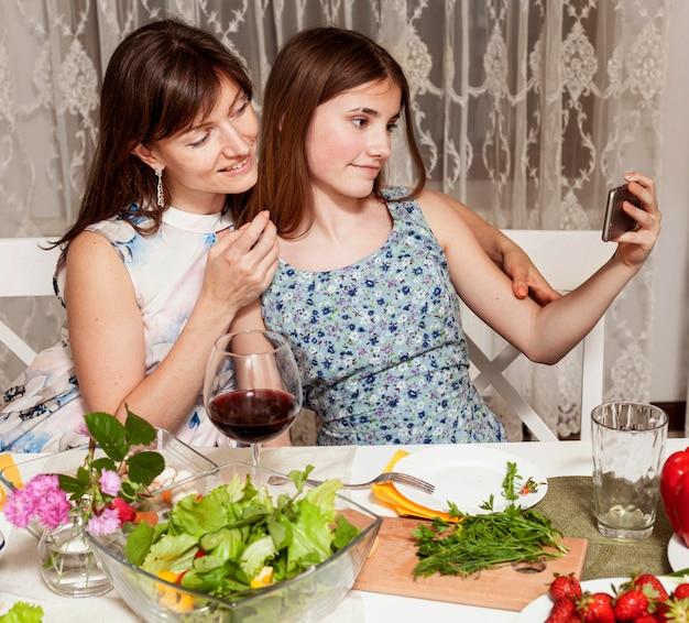 母と娘の夕食のテーブルでselfieを取って 無料写真