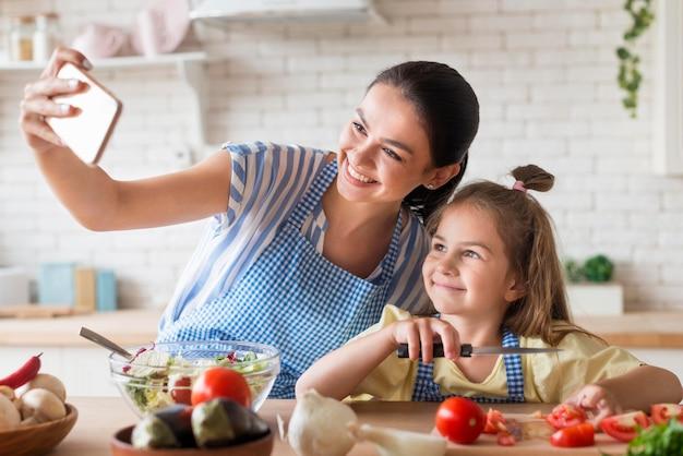 Мать и дочь, принимая селфи на кухне Бесплатные Фотографии