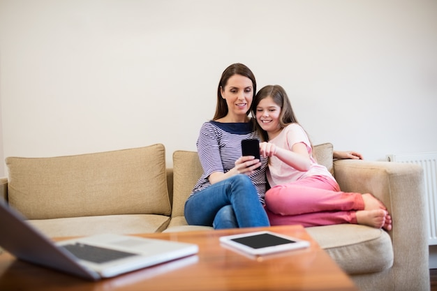 Mother and daughter using mobile in living room Free Photo