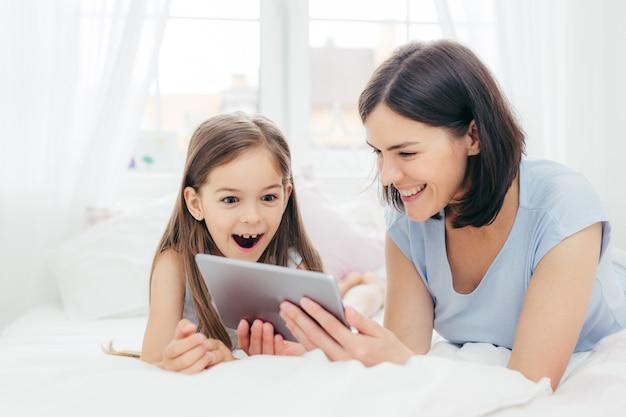 母と娘はタブレットコンピューターで何か面白いものを見る Premium写真