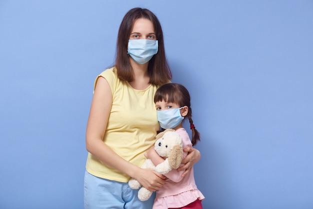 母と娘が医療用マスクを着用し、お互いをハグ Premium写真