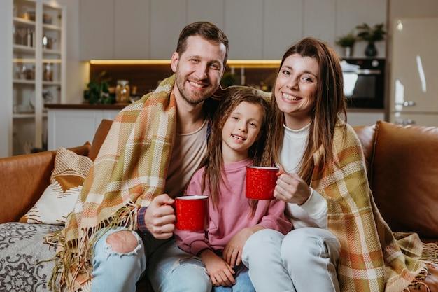 Мать и отец с теплыми напитками с дочерью дома Бесплатные Фотографии
