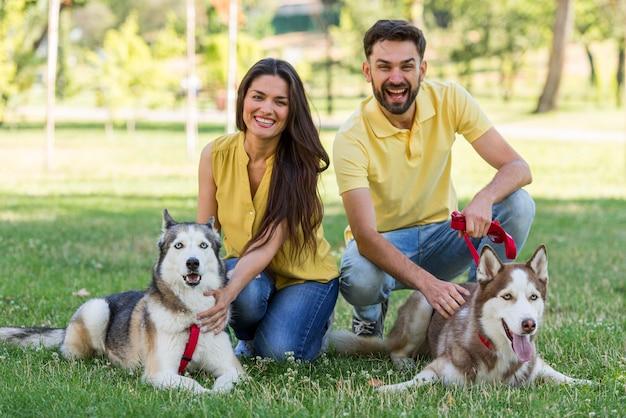 Мать и отец позируют со своими собаками в парке Бесплатные Фотографии