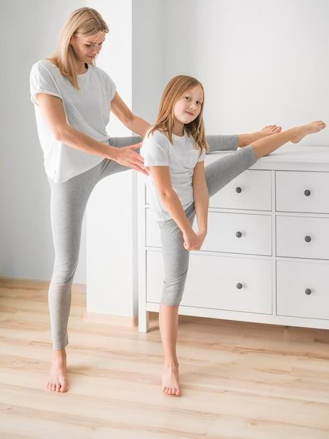 Мама и девушка дома растяжения Бесплатные Фотографии