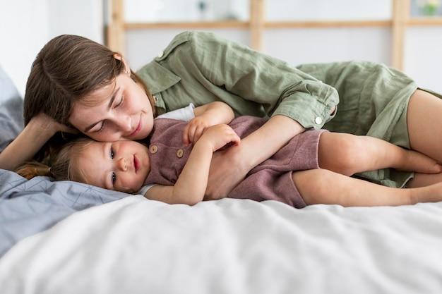 Мать и девочка лежат в постели Бесплатные Фотографии