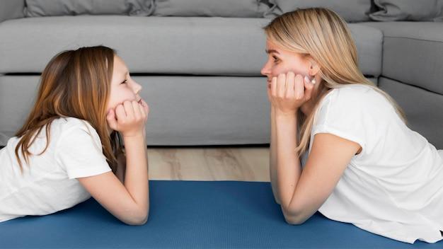 Мама и девушка тренируются на коврике Бесплатные Фотографии