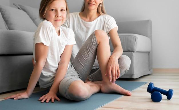 Мама и девочка тренируются с гантелями на коврике Бесплатные Фотографии