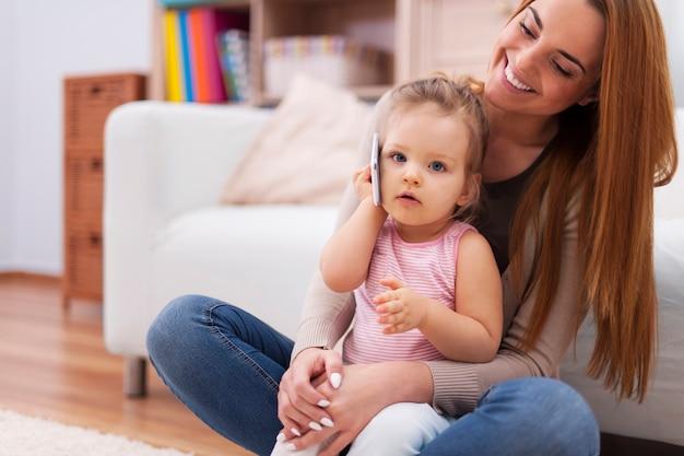 自宅で携帯電話を使用している母親と赤ちゃん 無料写真