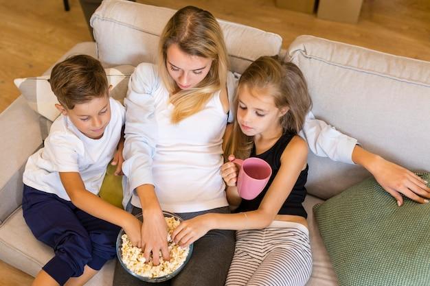 Мать и ее дети едят попкорн из миски Бесплатные Фотографии