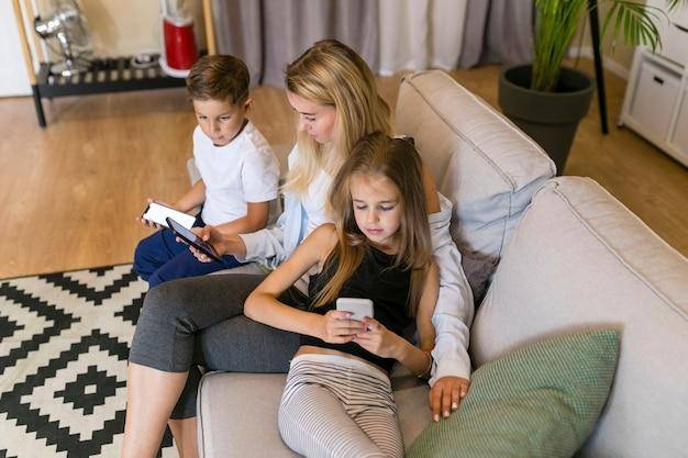 Мать и ее дети смотрят на свои телефоны Бесплатные Фотографии