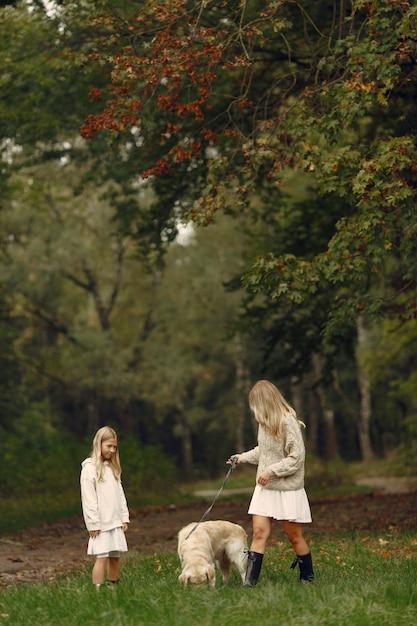 Мать и ее дочь играют с собакой. семья в осеннем парке. домашнее животное, домашнее животное и концепция образа жизни. осенняя пора. Бесплатные Фотографии